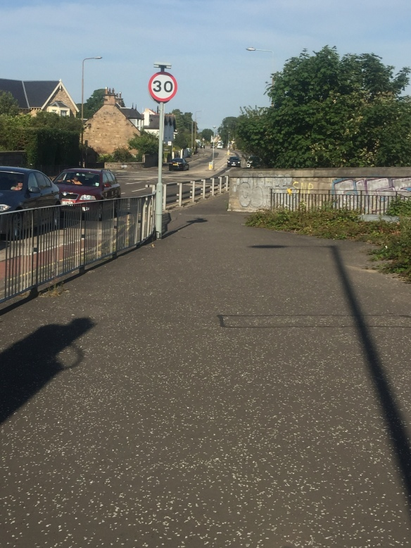 Fence protecting pedestrians from cars (good) but preventing access to Cyclepath from road (bad)